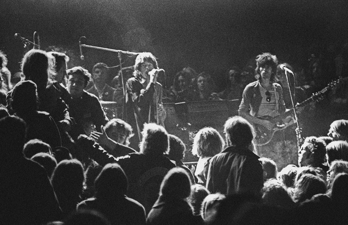 The Rolling Stones glance at the Hells Angels while performing onstage.
