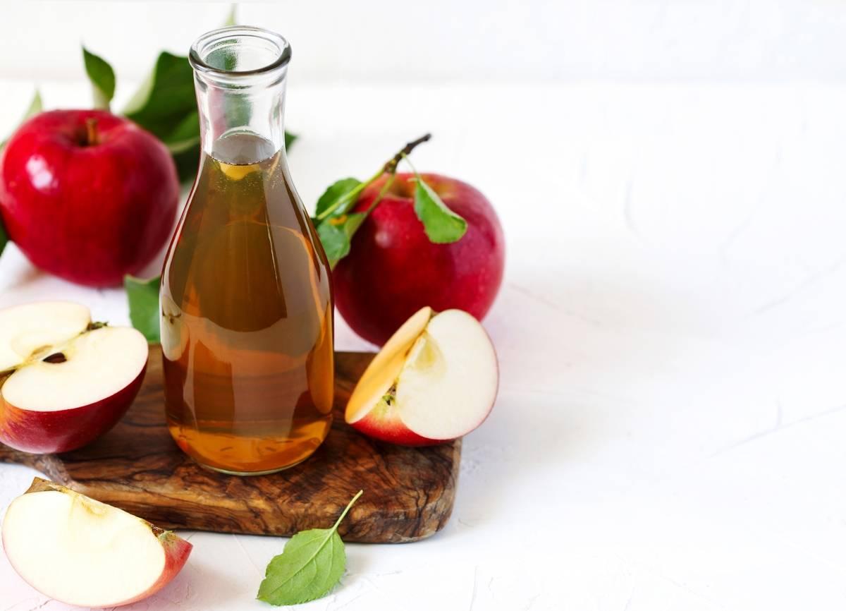 A glass jar of apple cider vinegar sits near apples.