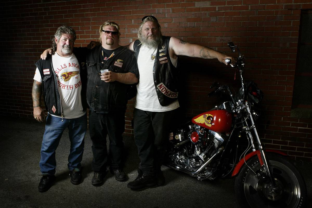 Hells Angels club members pose near a motorcycle together.