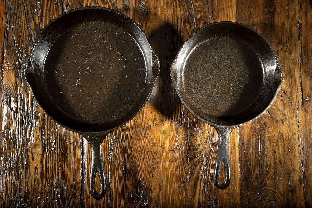 Two cast iron skillets sit next to each other.
