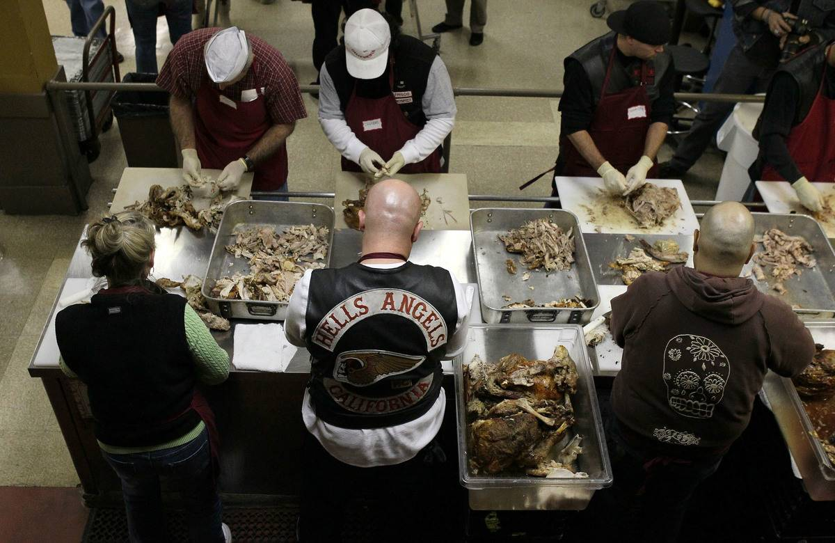 A member of Hells Angels helps volunteers to carve turkeys for the St. Anthony Foundation.