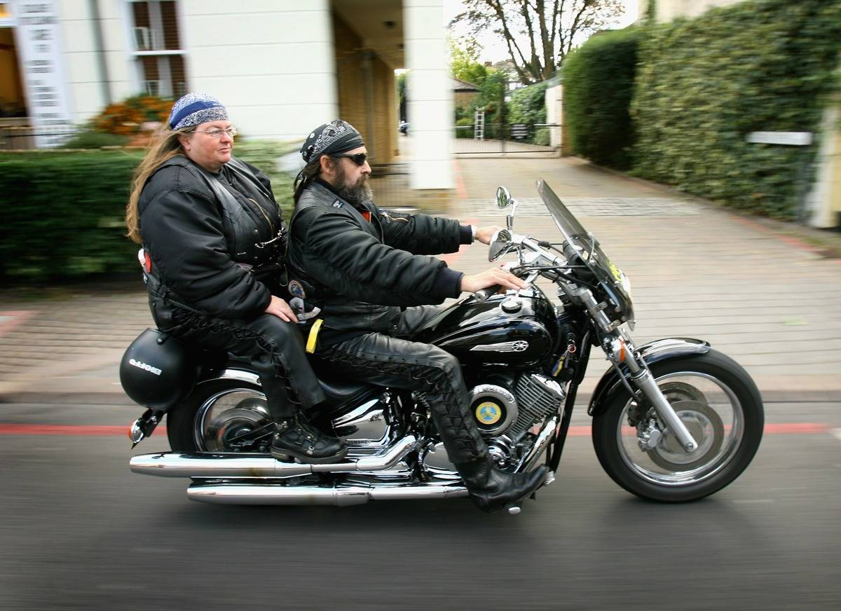 A Hells Angels member drives his motorcycle with his wife on the back.