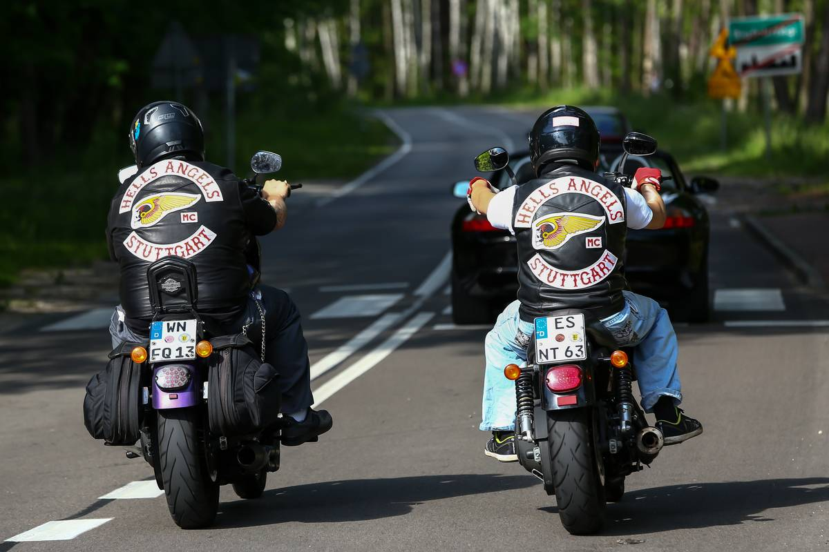 Two Hells Angels members drive motorcycles down the road.