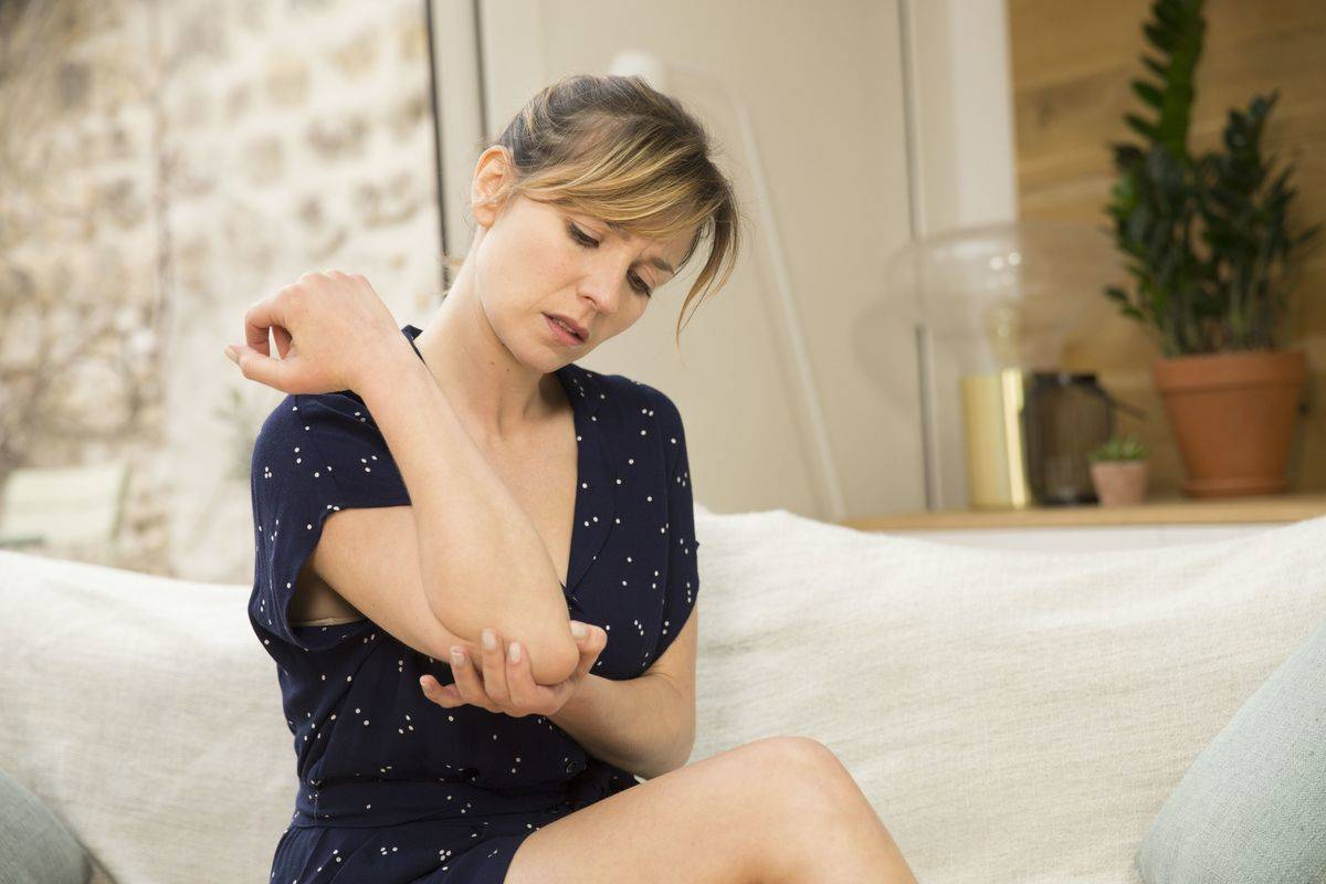 A woman rubs her aching elbow.