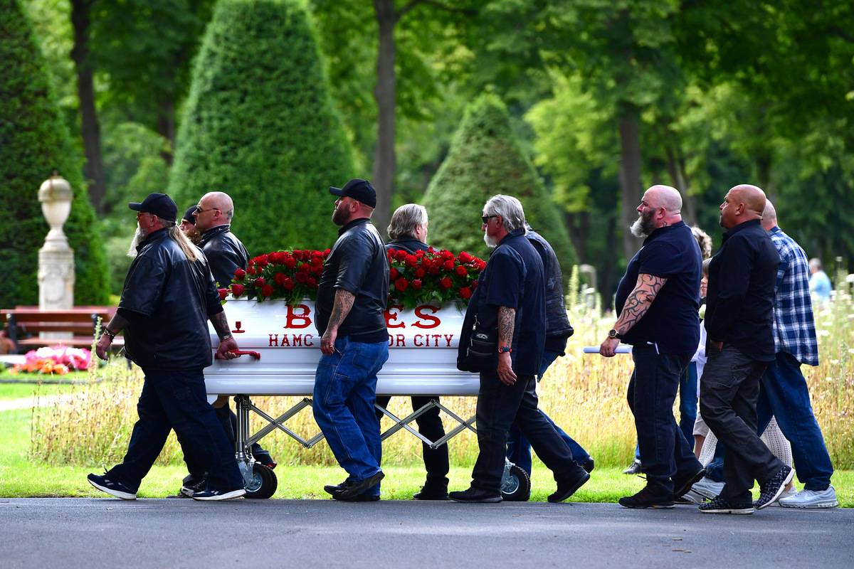 Hells Angels motorcycle club members escort a coffin during a funeral.