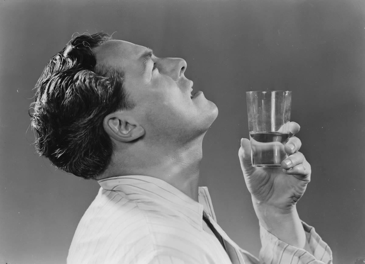 A man gargles a glass of water.