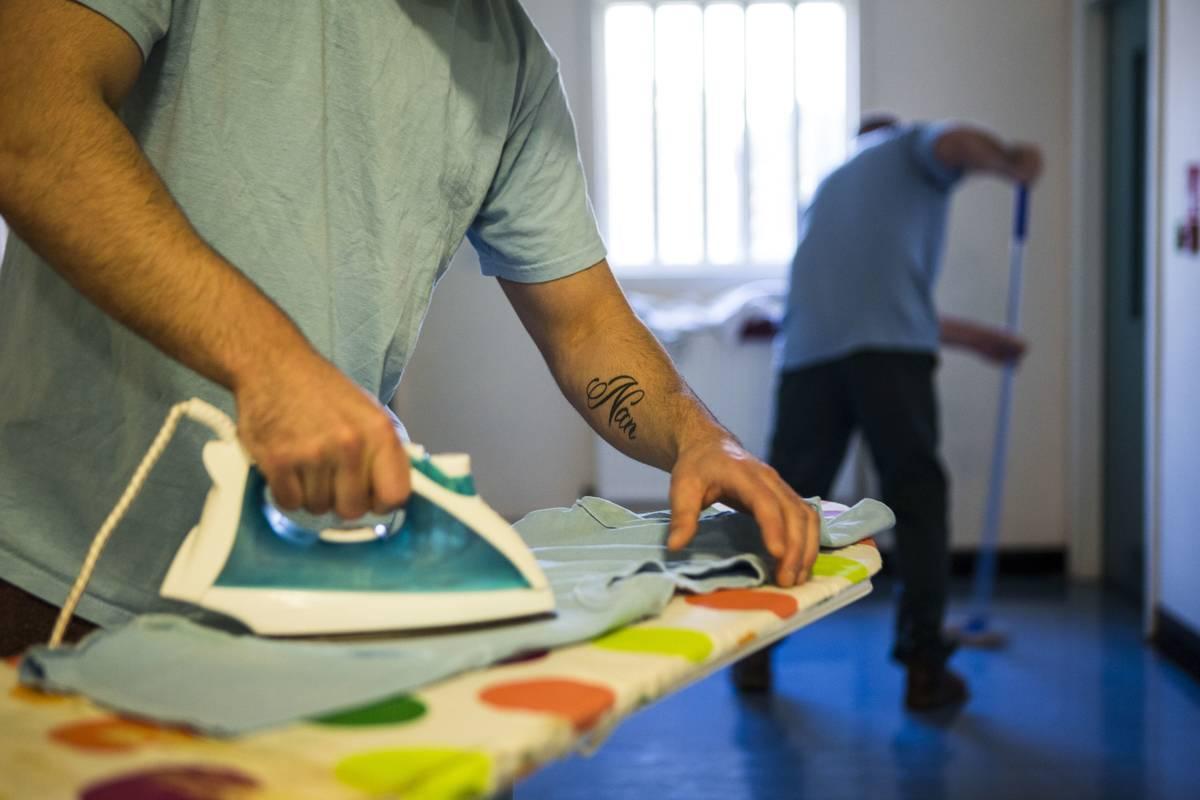 A man irons a shirt.