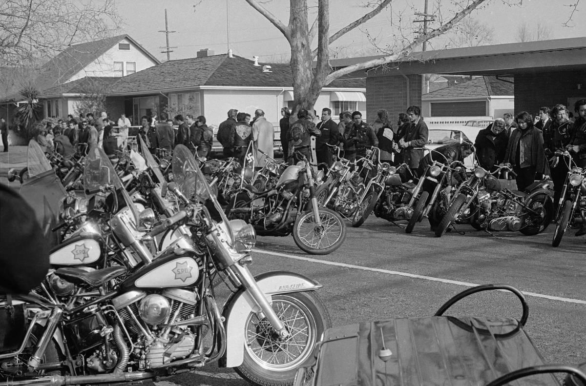 Dozens of Hells Angels members discard their motorcycles in the street.