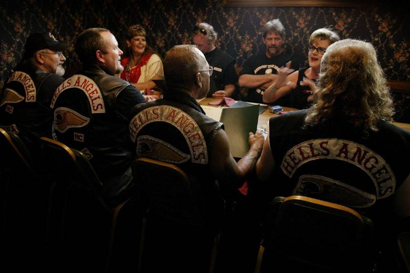 Members of Hells Angels sit at a table for a meeting.