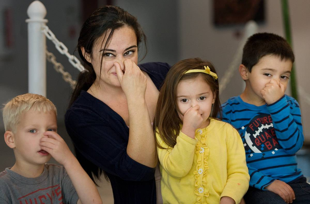 A mother and her kids pinch their noses.