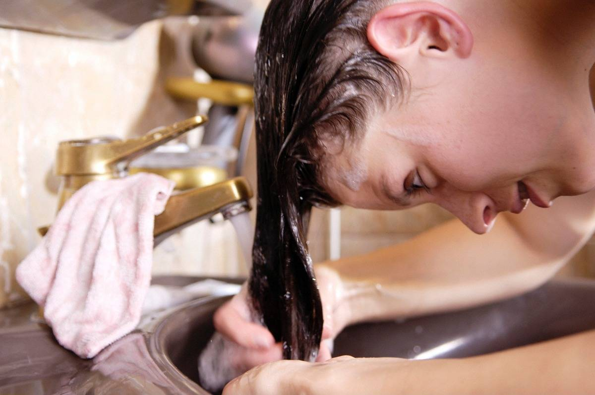A woman rinses her hair in the sink.