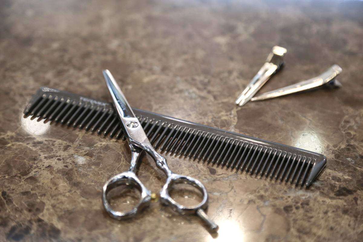 Barber scissors sit on a table with a comb.