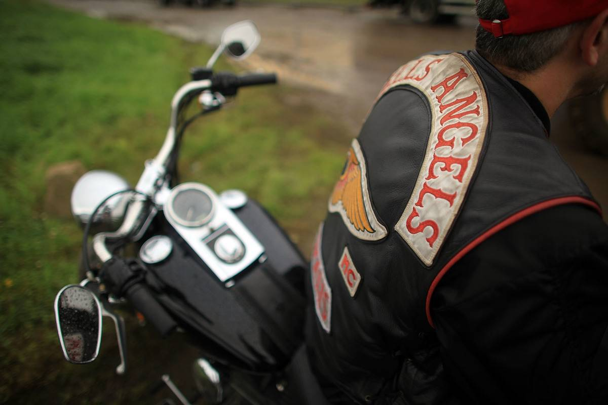 A view shows a Hells Angels member sitting on his bike with his back turned.