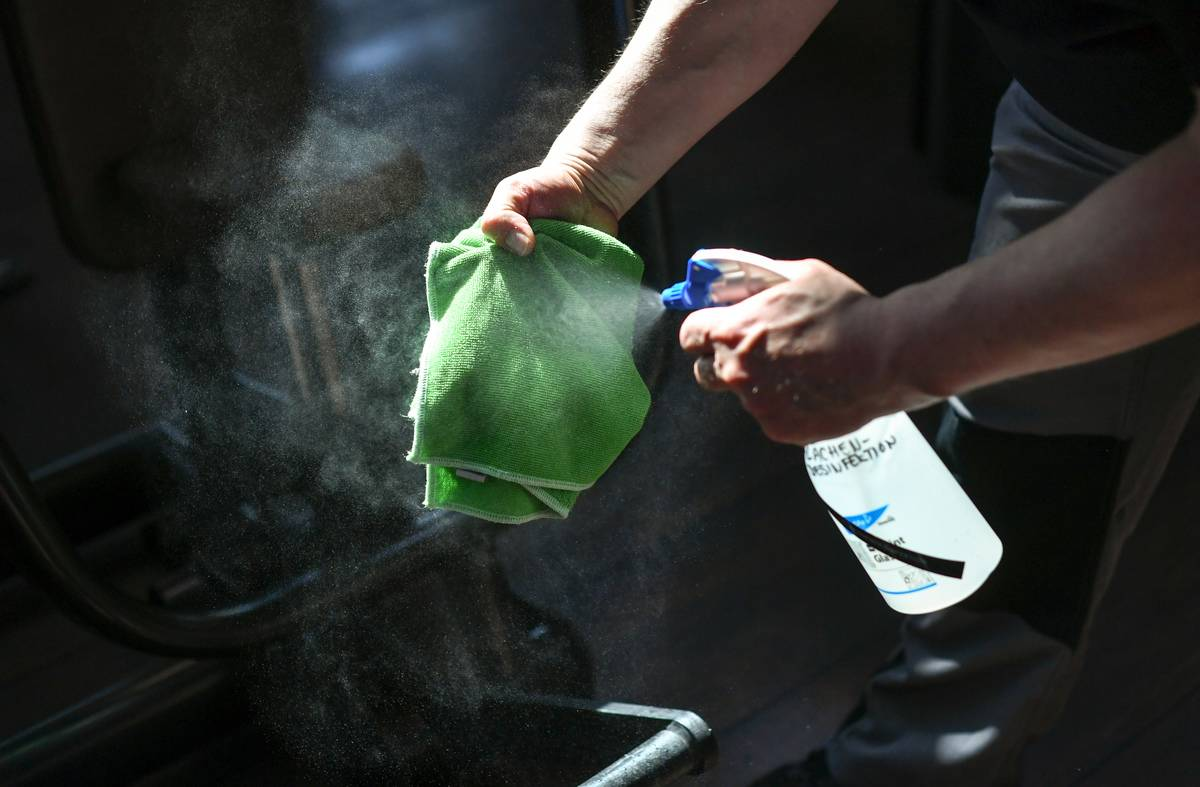A person sprays disinfectant onto a cleaning rag.