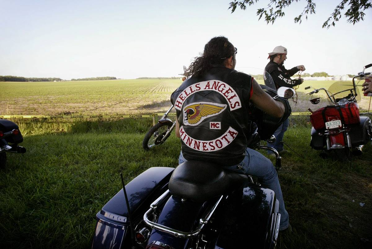 Bikers take off on their Harley David motorcycles on a grass hill.