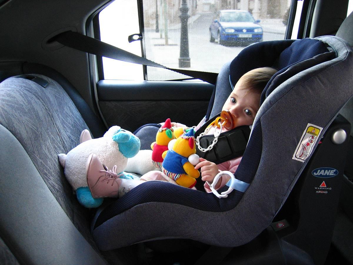 Toddler sitting in car seat.