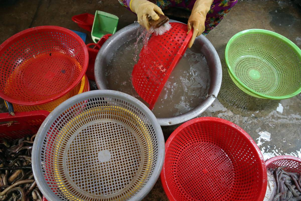 A woman washes strainers and pots.