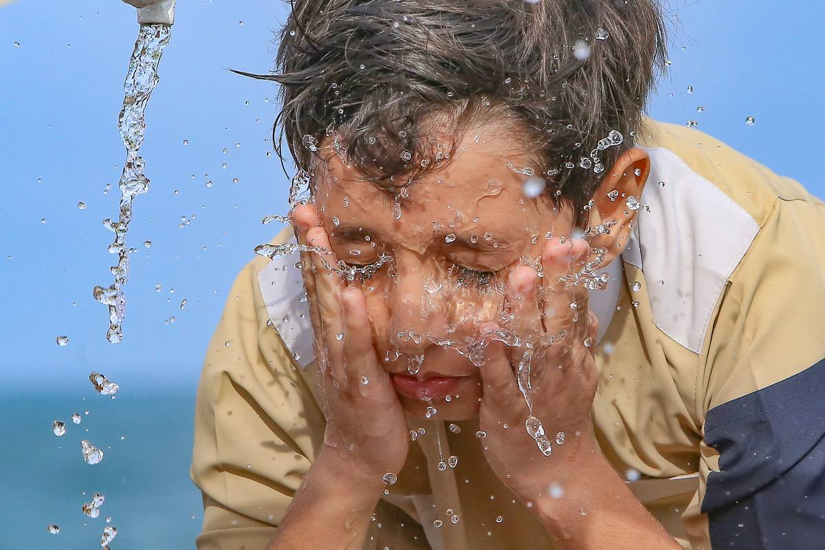 A boy splashes water on his face.