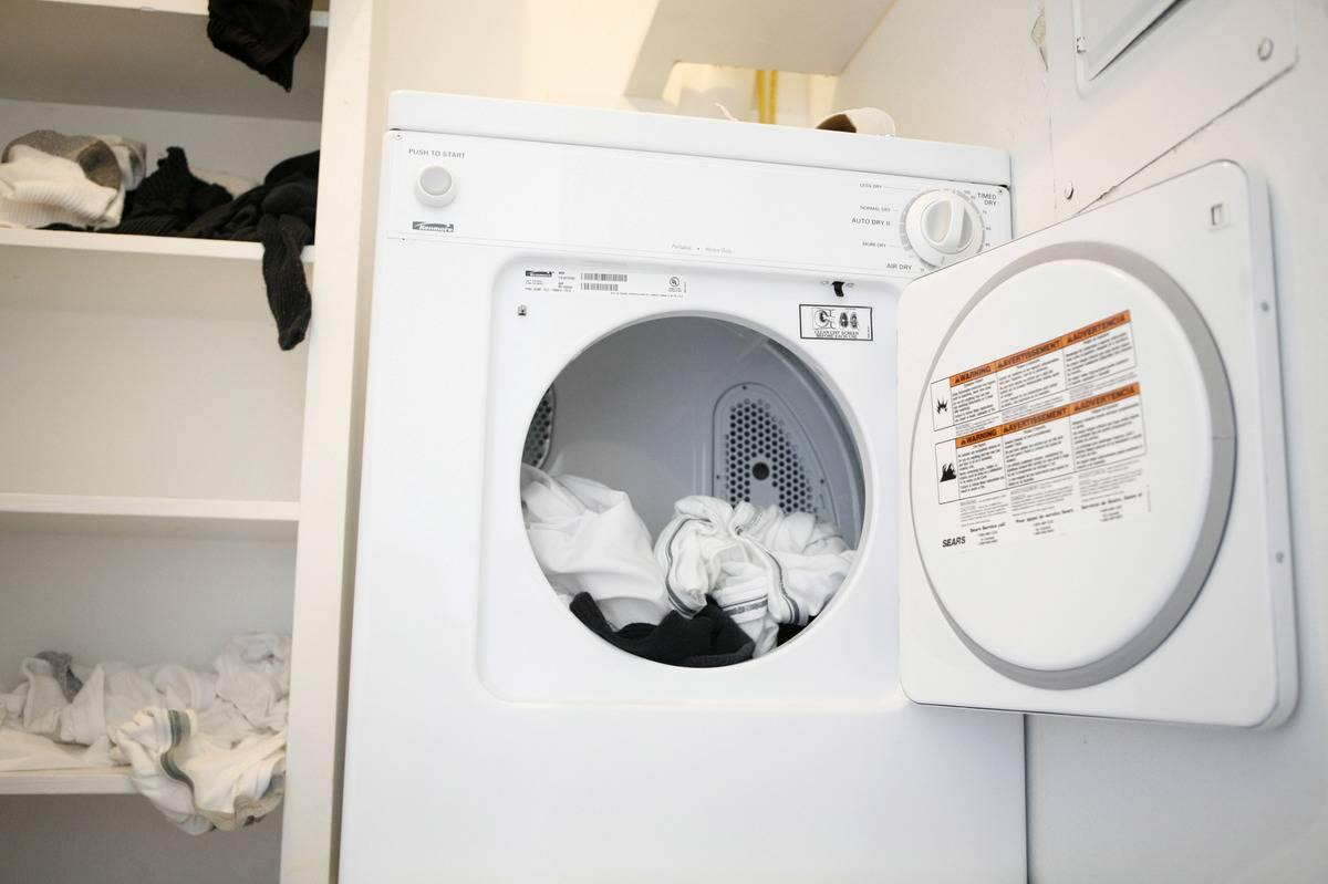 An open washing machine has clothes inside.