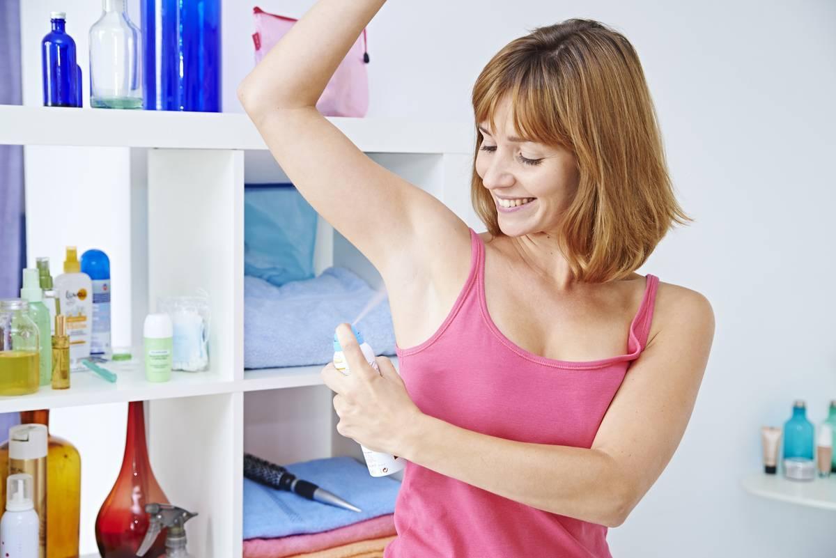 Woman applying spray deodorant