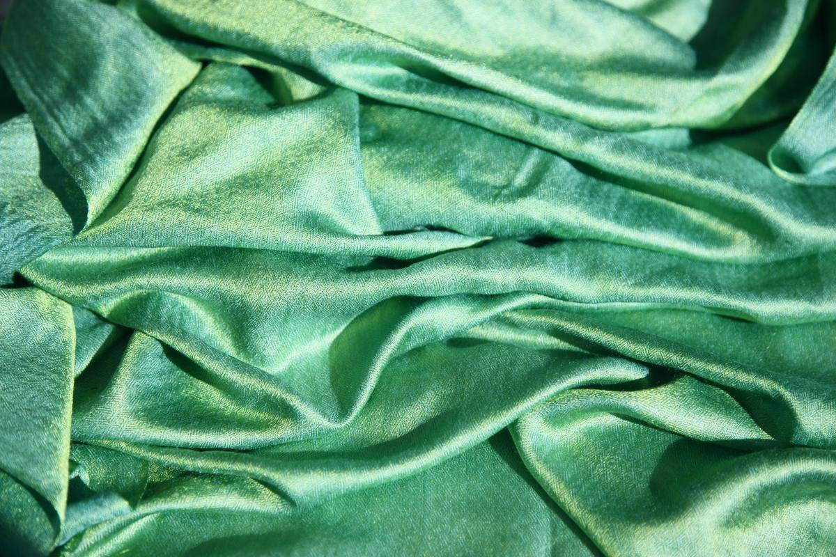 A close-up shows a wrinkled green silk shirt.