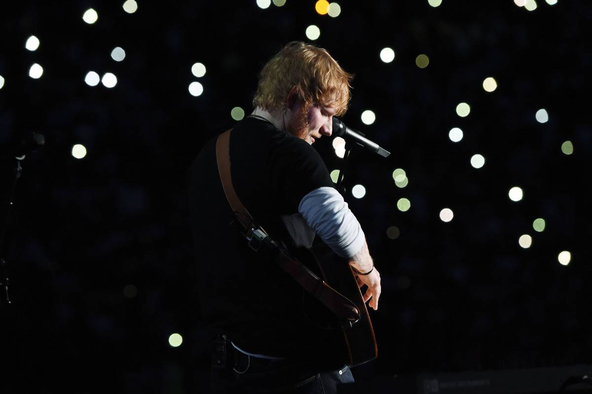 Ed Sheeran plays guitar onstage with star-like lights behind him, 2018.