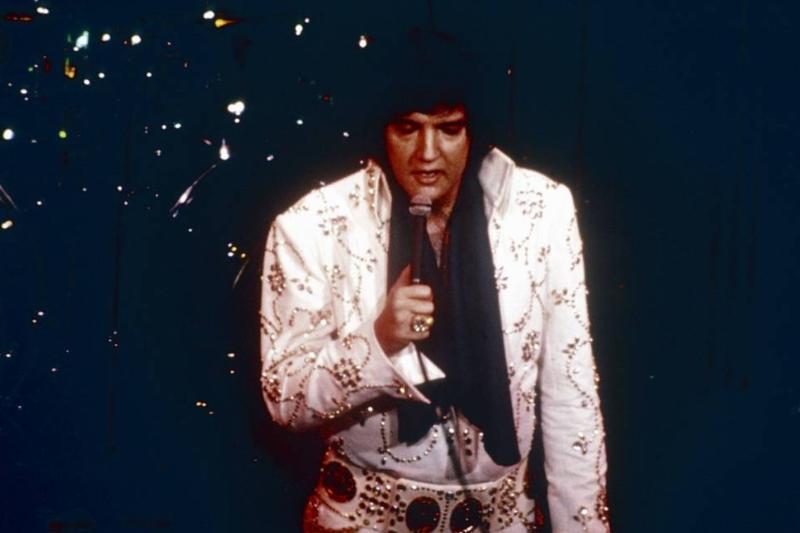 Elvis Presley sings on a dark stage, 1972.