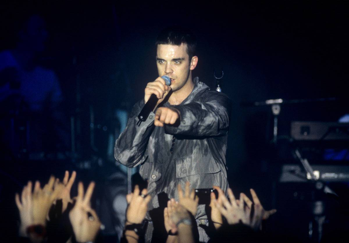 Robbie Williams sings in front of a crowd in 1997.