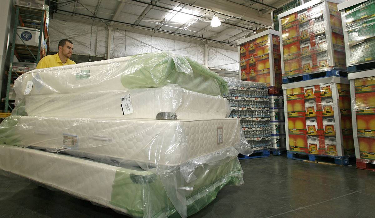 A Costco employee hauls four mattresses into the store.