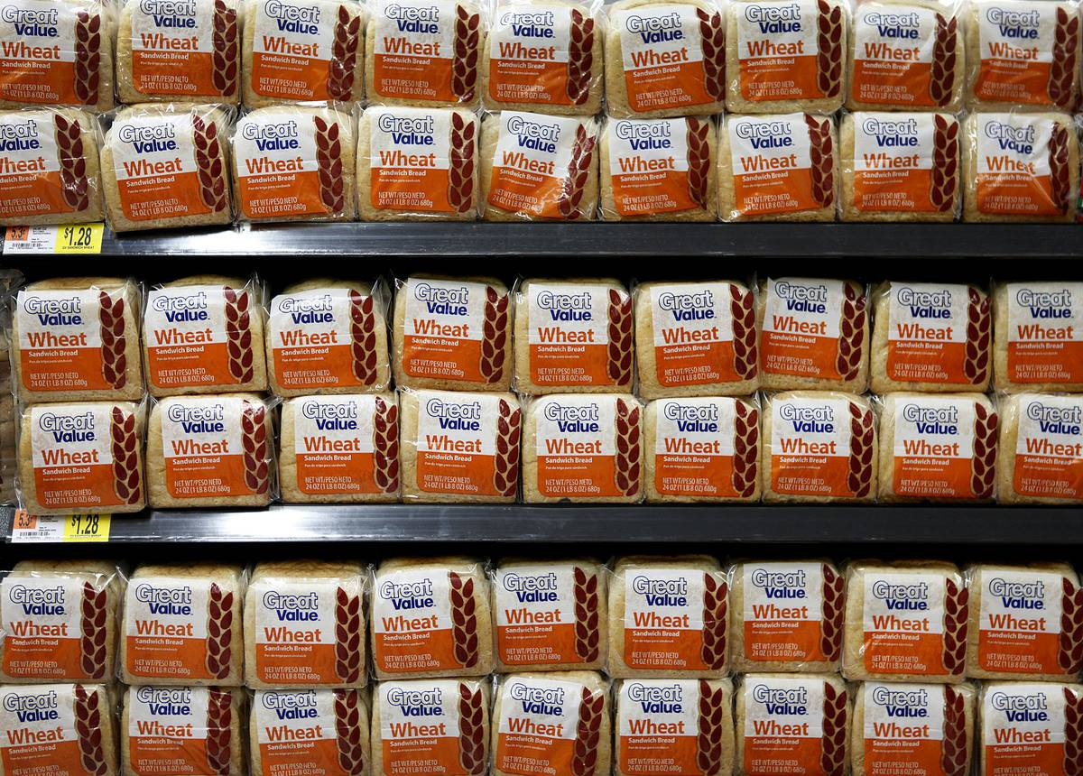 Packages of Great Value Bread are stacked on shelves at Walmart.