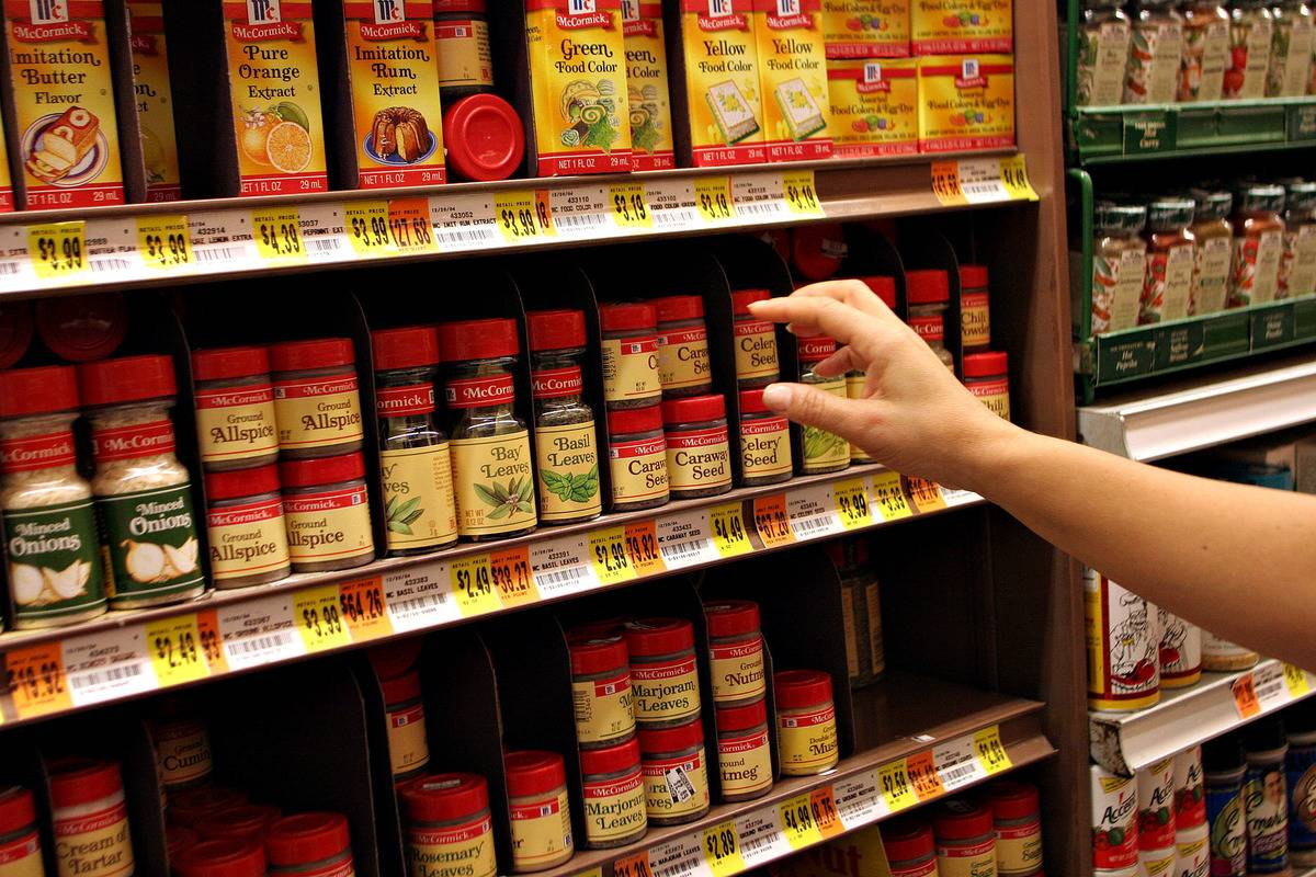 A shopper reaches toward a display of McCormick spices at a supermarket.