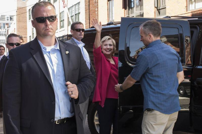 Hillary Clinton is guarded by U.S. Secret Service as she enters her Chevy Suburban.
