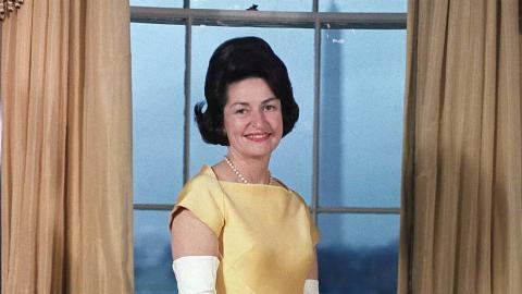 Lady Bird Johnson poses in front of a window.