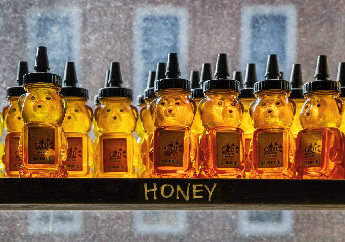Honey bear containers sit next to a window on a shelf labeled