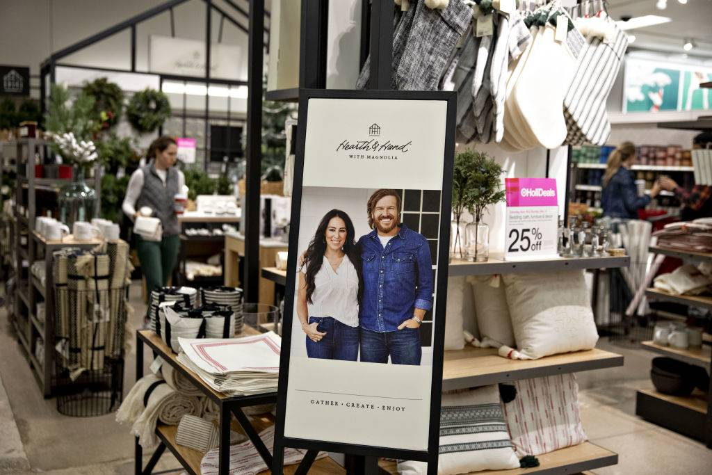 A sign featuring HGTV's Fixer Upper hosts Chip and Joanna Gaines is seen in front of a
