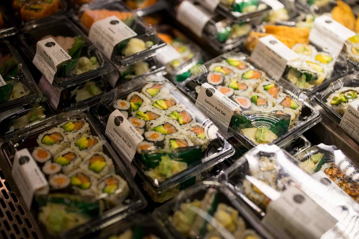Packages of premade sushi are displayed at a grocery store.