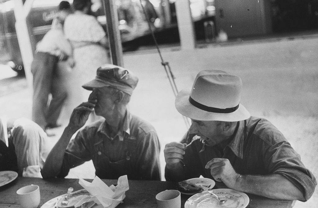 Black and white photograph of spectators at a county fair eating lunch