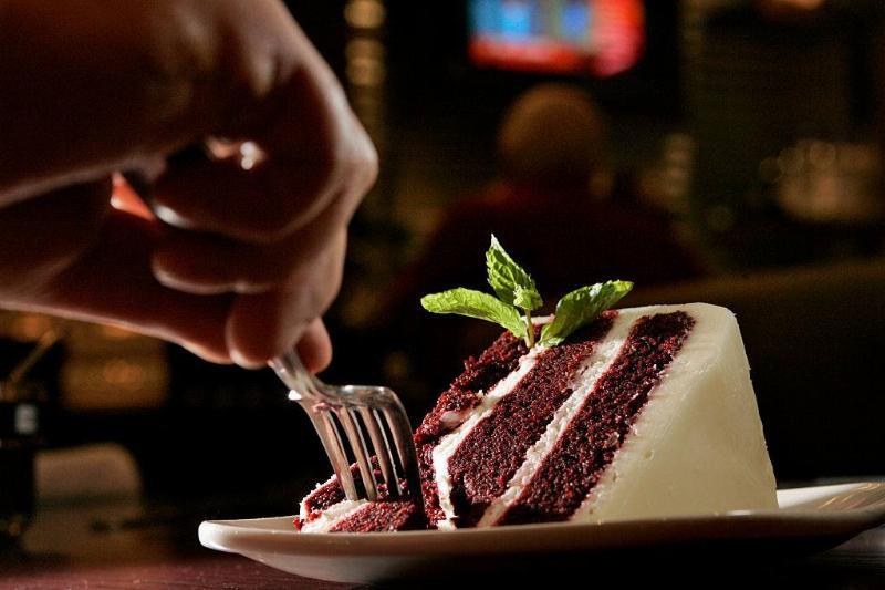 eating red velvet cake with mint with a fork