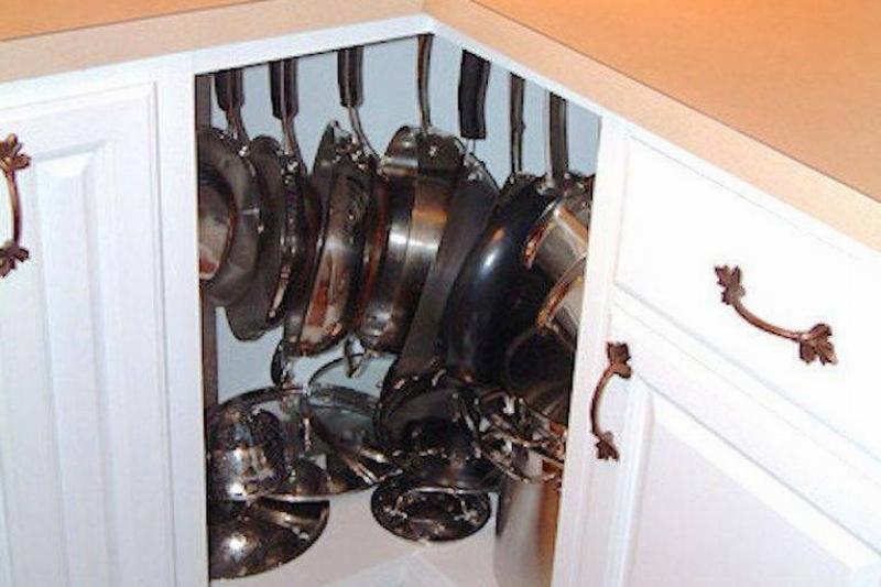 Pots hang inside of a corner cabinet.