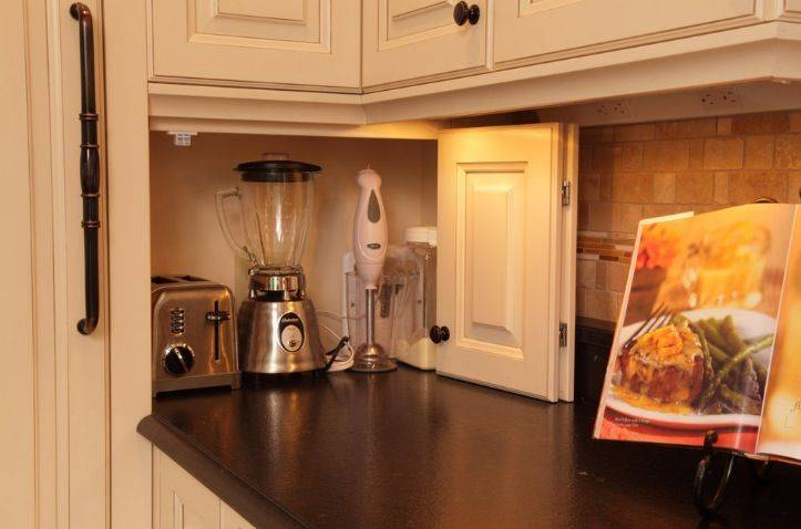 A door opens to reveal appliances on the kitchen counter.