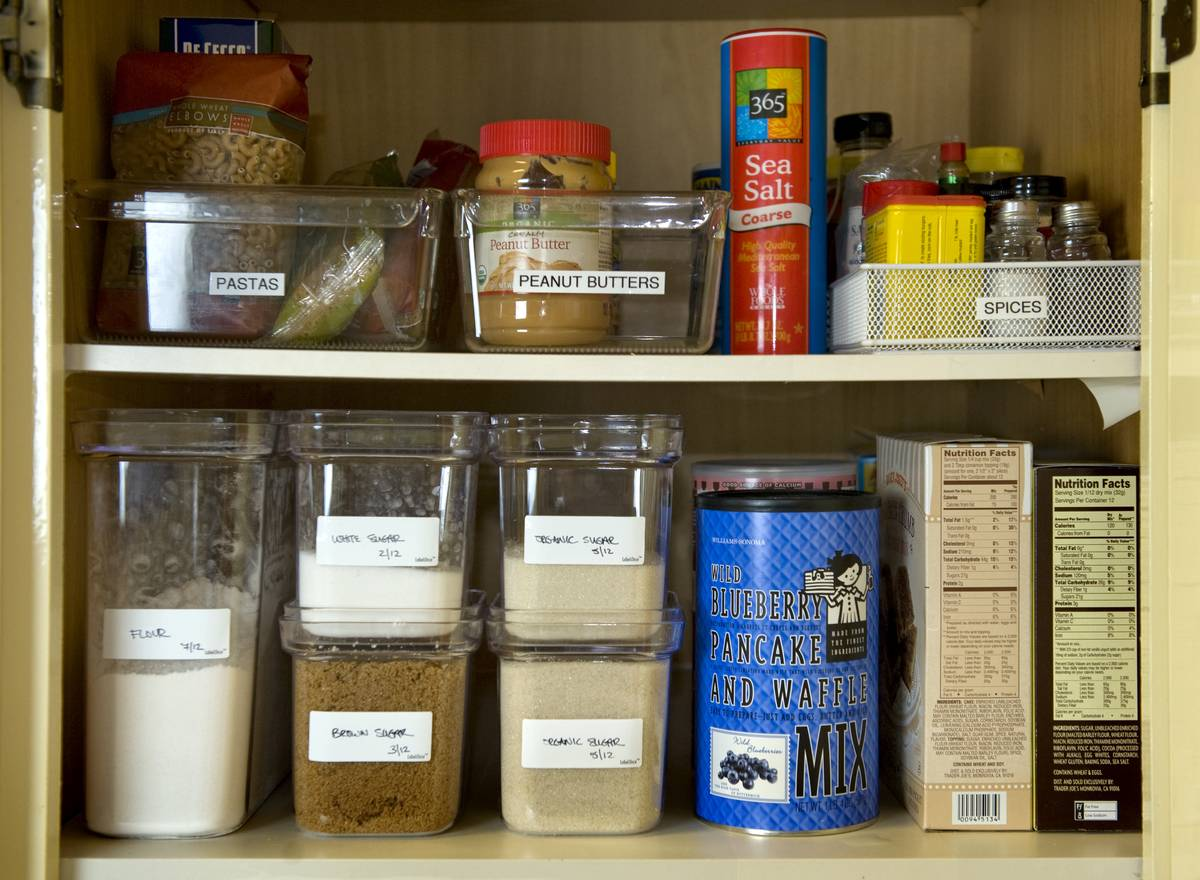 A pantry is organized with clear, labeled food containers.