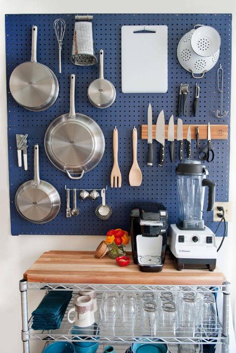 A blue pegboard holds pots, knives, and kitchen utensils.
