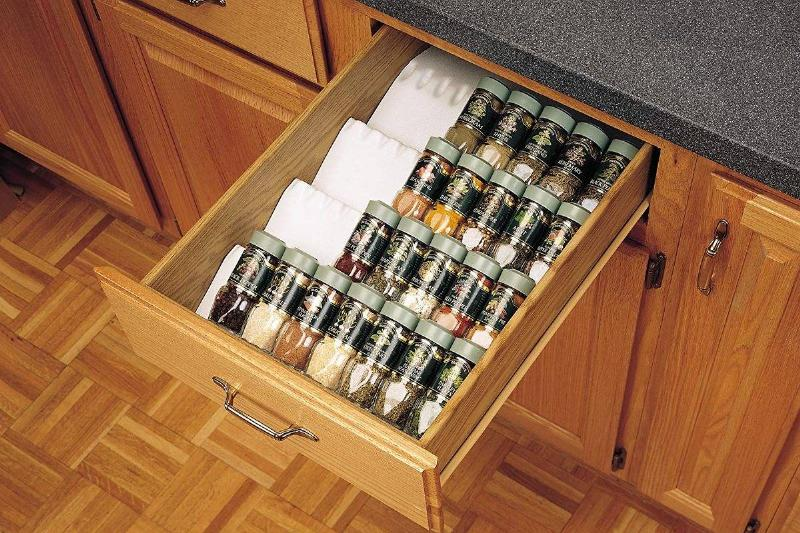 Spice containers are organized inside of a drawer.