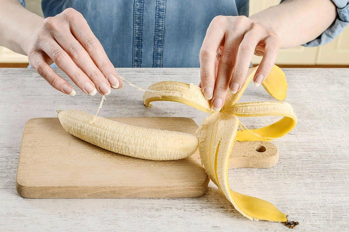 A woman pulls a string off of a peeled banana.