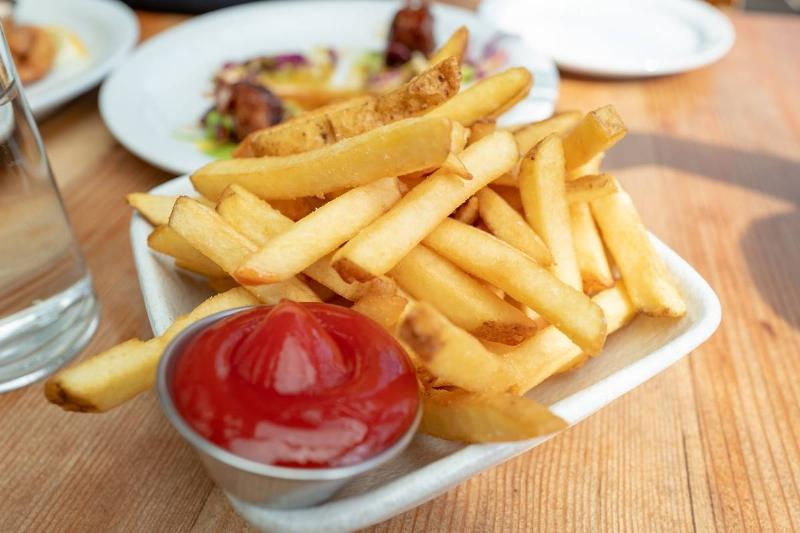 A tiny cup holds ketchup for french fries in a restaurant.