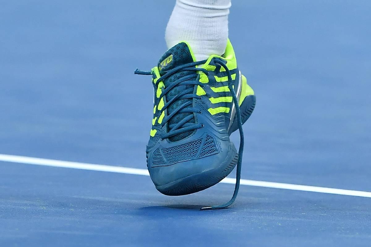 A broken shoelace is seen under a tennis player's shoe.