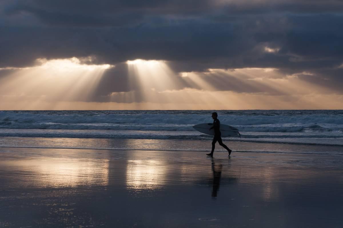 Sun rays shine through clouds onto a beach where a man with a surf board walks.