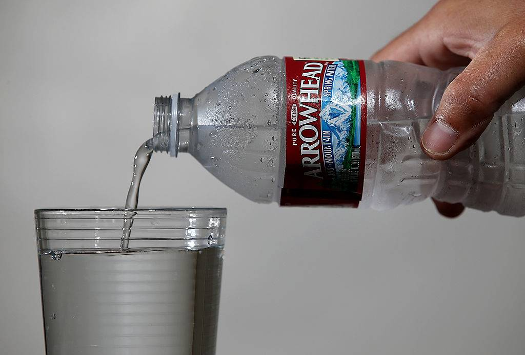 A bottle of Arrowhead water is poured into a glass