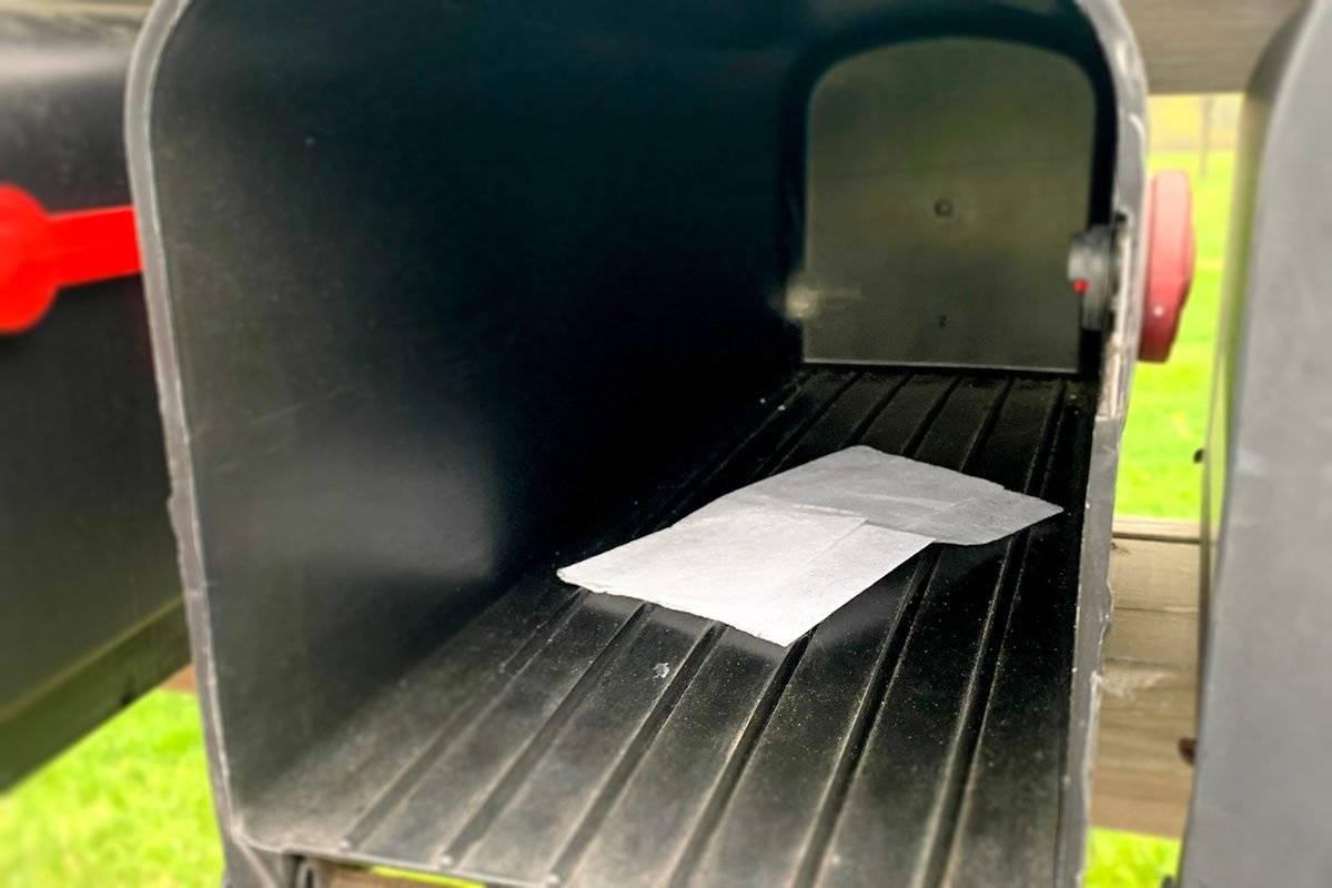 A dryer sheet is inside a black mailbox.