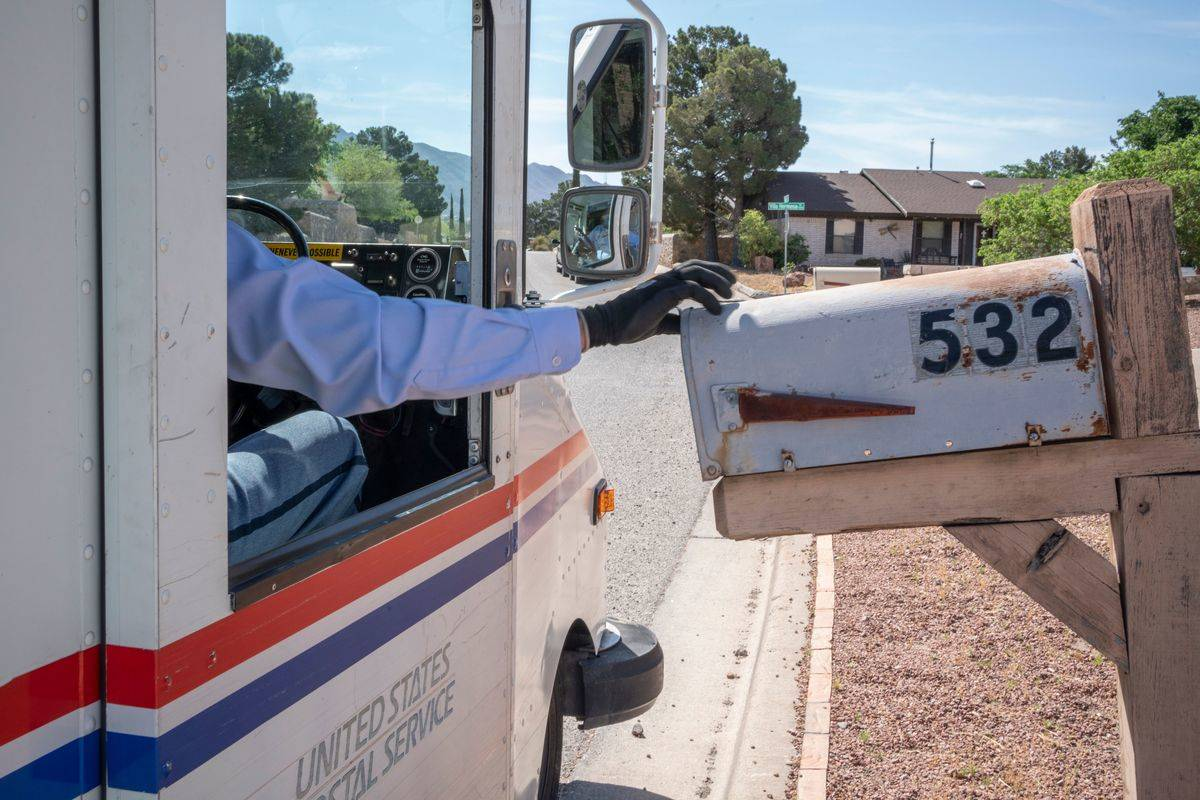 A delivery driver opens a person's mailbox.